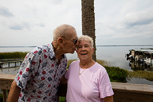 An older man leans in to kiss the face of a smiling older woman, both of them in front of a lake with a marina and boat dock in view